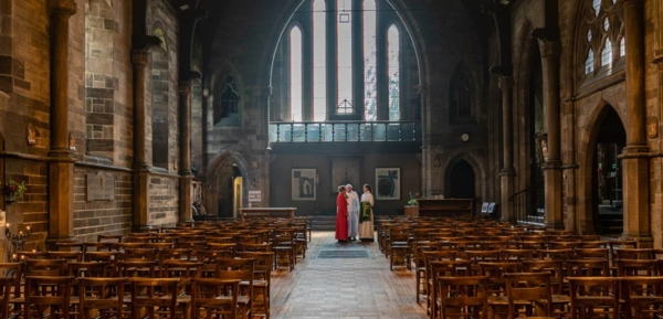 View from front of nave to rear of church with three people preparing for mass.