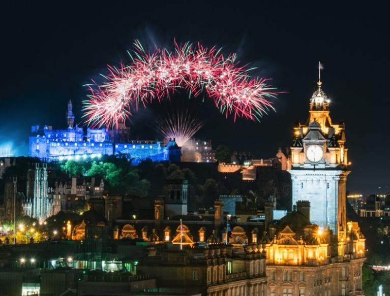 Fireworks in night sky over Edinburgh castle and Princes Street.
